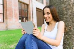 Joyful young woman using gadget outdoors Stock Image