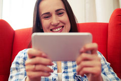 Joyful young woman using her smartphone. And smiling Stock Images