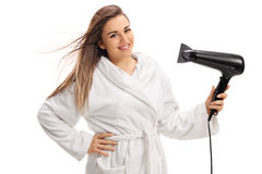 Joyful young woman wearing a bathrobe and drying her hair with a Stock Photo
