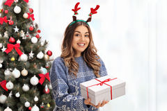 Joyful young woman wearing red antlers and holding a present Royalty Free Stock Images