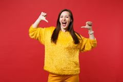 Joyful young woman in yellow fur sweater keeping mouth wide open, pointing thumbs on herself isolated on red wall. Background in studio. People sincere emotions stock photography