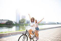 Joyful young women riding a bicycle together. Best friends having fun on a bike at the river promenade in the cit. Joyful young women riding a bicycle together stock image
