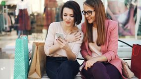 Joyful young women are using smartphone together looking at screen smiling and laughing resting on bench in shopping