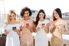 Joyful young women using their smartphones Stock Photos