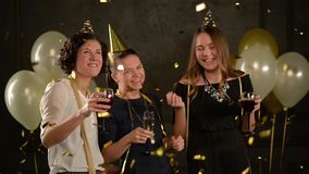 Joyful Young Women Wishing Happy Birthday to Their Friend among Golden Confetti. Cute Girls Celebrate at a Party Holding stock video