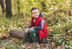 Joyfull boy sitting on log in the forest Royalty Free Stock Image