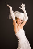Joyfull bride. Dressed in retro style with her arms raised,on the black background stock photography
