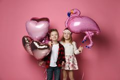 Joyfull Little Boy With Color Heart Balloons And Nice Little Girl With Flamingo Balloon Came Together At The Party Stock Photo