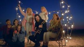 Joyfullweekend, bedrijf van gitaar spelen en vrienden die terwijl het ontspannen op strand in avond zingen stock videobeelden