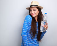 Joying casual woman in summer hat holding bottle of pure water a Royalty Free Stock Photography