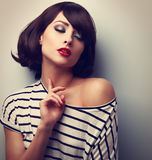 Joying young model touching skin with closed eyes in trendy blou Royalty Free Stock Photo