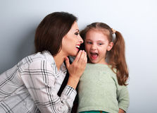 Joying young mother whispering the secret to her funny grimacing Stock Images