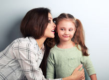 Joying young mother whispering the secret to her funny grimacing. Daughter in ear in studio royalty free stock photos