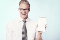 Joyous affärsman som framlägger tom anteckningsbok. arkivbild