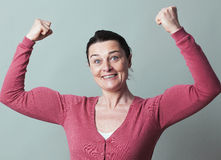 Joyous beautiful 40s woman flexing her muscles up Stock Image
