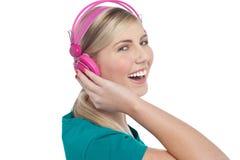 Joyous blont teen lyssna till livlig musik Arkivfoto