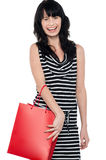 Joyous brunette posing with red shopping bag Royalty Free Stock Image