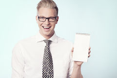 Joyous businessman presenting blank notepad. Stock Photography