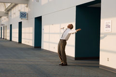 Joyous businessman standing outside meeting room, arms out and head back, smiling, side view Stock Photos