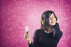 Joyous calm girl enjoying listening to music with headphones. Stock Photo