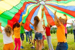 Joyous classmates jumping under colorful parachute in the summer outdoors. Joyous classmates laughing, jumping under colorful parachute, trying to touch it stock photography