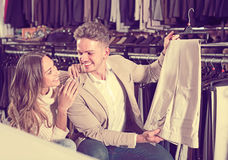 Joyous couple choosing new trousers in cloths store Stock Photo