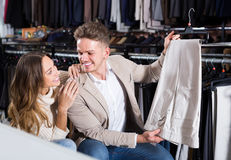 Joyous couple choosing new trousers in cloths store. Joyous couple choosing new trousers in men's cloths store Royalty Free Stock Photography