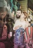 Joyous couple examining rucksacks in sports equipment store royalty free stock image