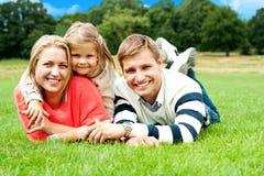 Joyous familj i en park som ut tycker om dag royaltyfria bilder