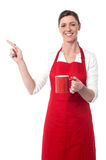 Joyous female with coffee mug pointing away Royalty Free Stock Photography
