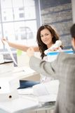 Joyous female passing phone to colleague in office Royalty Free Stock Photos