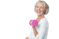 Joyous fit woman lifting dumbbells. Senior woman in gym working out with dumbbells Stock Photo