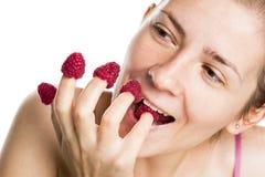 Joyous flicka som äter hallon från fingrar. royaltyfri bild