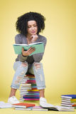 Joyous focused girl studying with multicolored books. Royalty Free Stock Photo