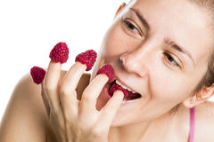 Joyous girl eating raspberries from fingers. Royalty Free Stock Image