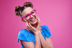 Joyous girl with two buns wearing pink glasses Stock Photography