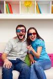 Couple hållande ögonen på komedi och skratta Royaltyfria Foton