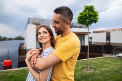 Cheerful couple hugging while standing near water stock photo