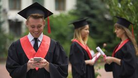 Joyous male graduate typing message on smartphone, browsing mobile applications. Stock footage stock video