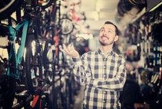 Joyous man in bicycle shop chooses for himself sports bike Royalty Free Stock Photography