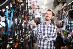 Joyous man in bicycle shop chooses for himself sports bike Stock Photos