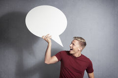 Joyous man holding empty speech balloon. Stock Image