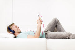 Joyous man listening to music with earphones and resting. Royalty Free Stock Photos