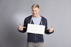Joyous man pointing fingers at blank signboard. Royalty Free Stock Photo