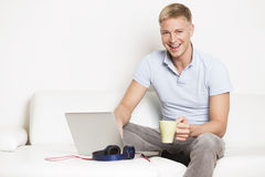 Joyous man sitting on couch with laptop and drinking coffee. stock image