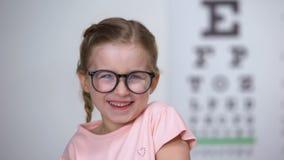 Joyous meisje die in oogglazen, de positieve resultaten van de visiebehandeling lachen stock footage