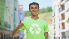 Joyous mixed-race teen in recycling symbol t-shirt gesturing thumbs-up, ecology