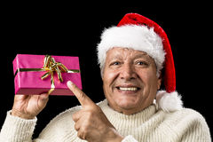 Joyous Old Man Pointing At Magenta Wrapped Gift. Bright aged gentleman in party mood wearing a Santa Claus cap. He is pointing his left index finger at a magenta Stock Photography