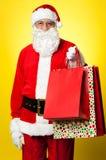 Joyous Santa som poserar med färgrika shoppingpåsar royaltyfria foton