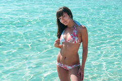Joyous slim woman in bikini with beauty body standing in sea. Joyous slim woman in bikini with beauty body standing in water Royalty Free Stock Image